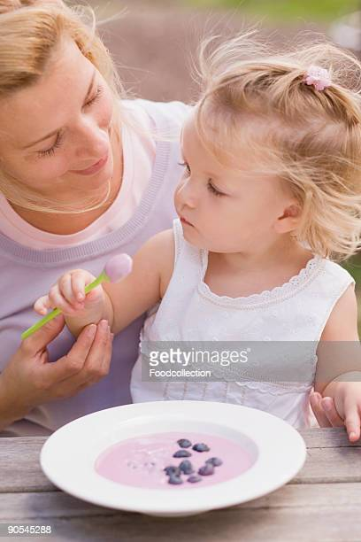 Mother and daughter (2-3) with dish of blueberry yoghurt