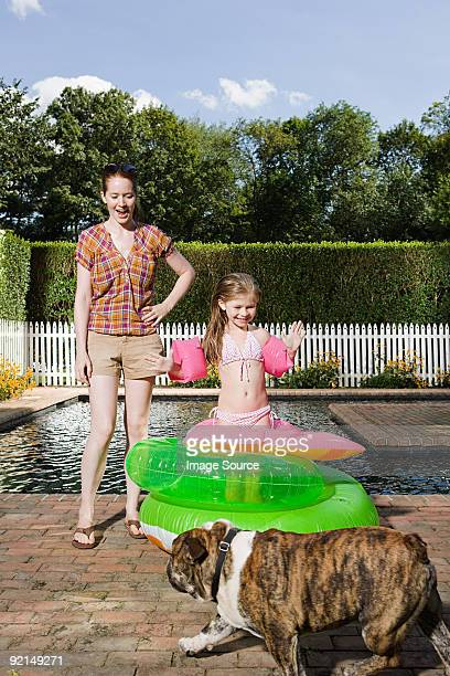 Mère et fille avec un chien bord de la piscine