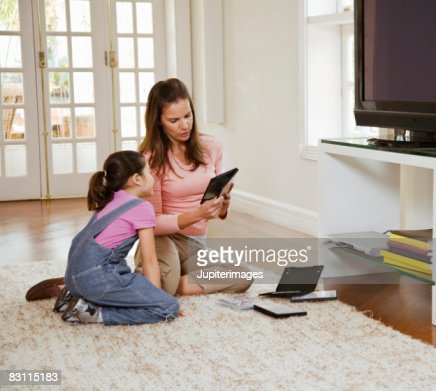 Mother and daughter with DVDs at home : Stock Photo