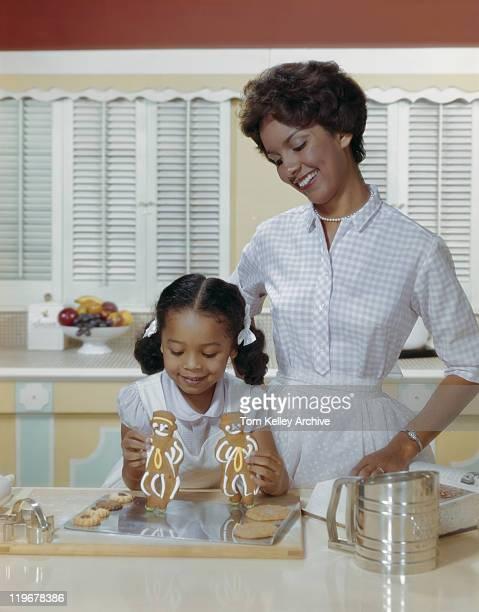 Mère et fille de pain d'épice avec des biscuits, souriant