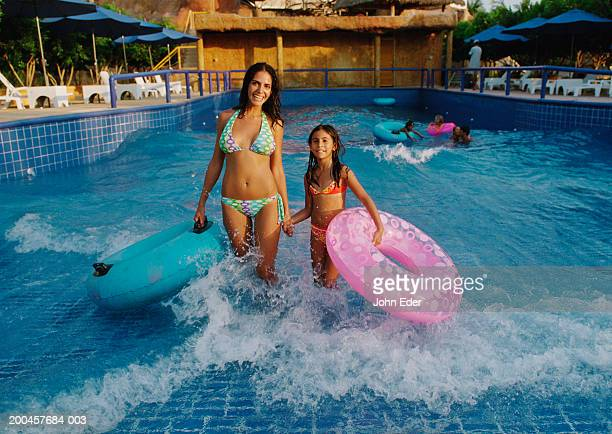 Mother and daughter (9-11) with inner tubes in water park