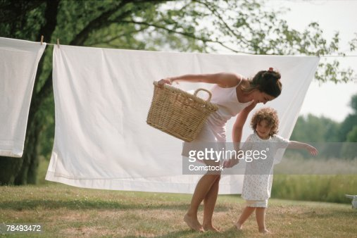 Mother and daughter with laundry on clothesline : Stock Photo