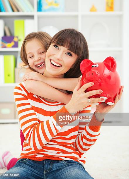 Mother and daughter with piggy bank.