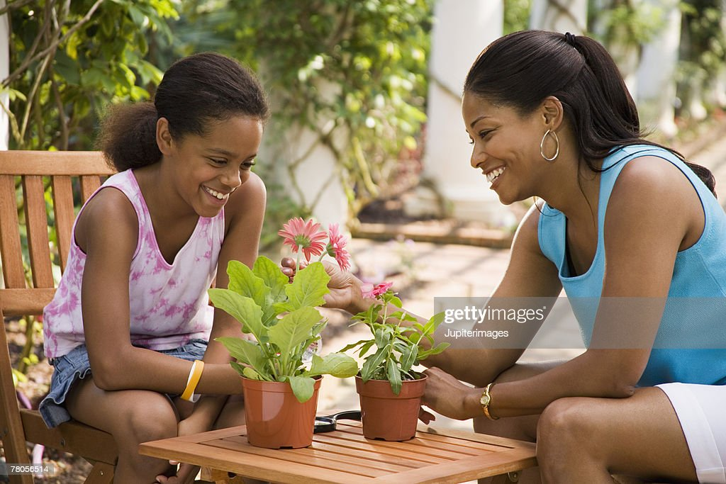 Mother and daughter with potted flowers : Stock Photo