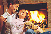 Mother and daughter with puppy by fireplace