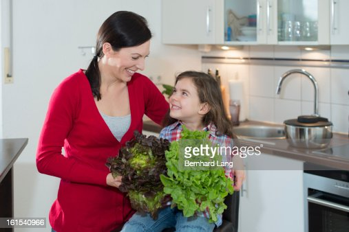 Mother and daughter with salads in a kitchen : Stock Photo