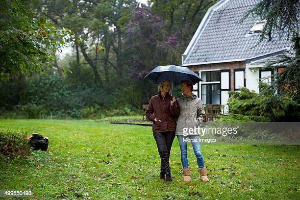 Mother and daughter with umbrella outside cottage