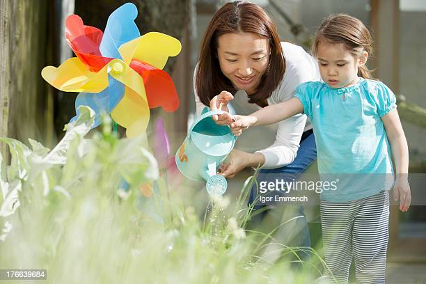 Mother and daughter with watering can and toy windmill