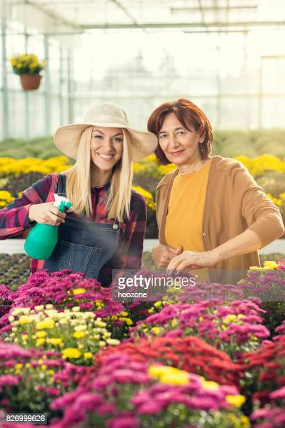 Mother and daughter working at greenhouse