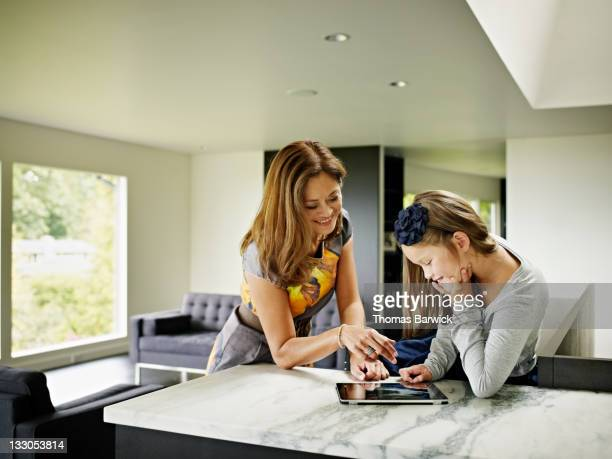 Mother and daughter working on digital tablet