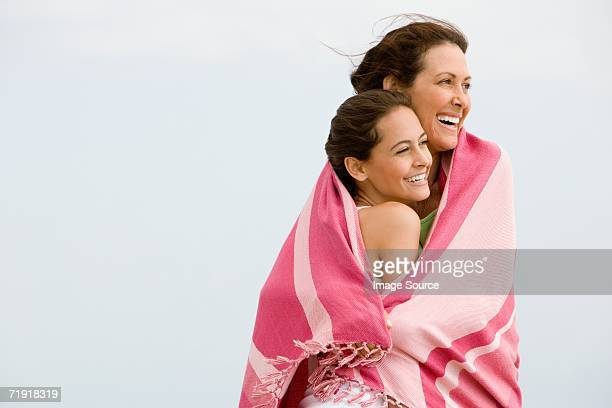 Mother and daughter wrapped in a blanket