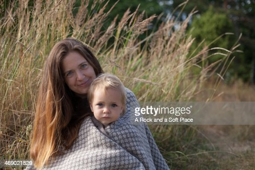 Mother and daughter wrapped in blanket in grass