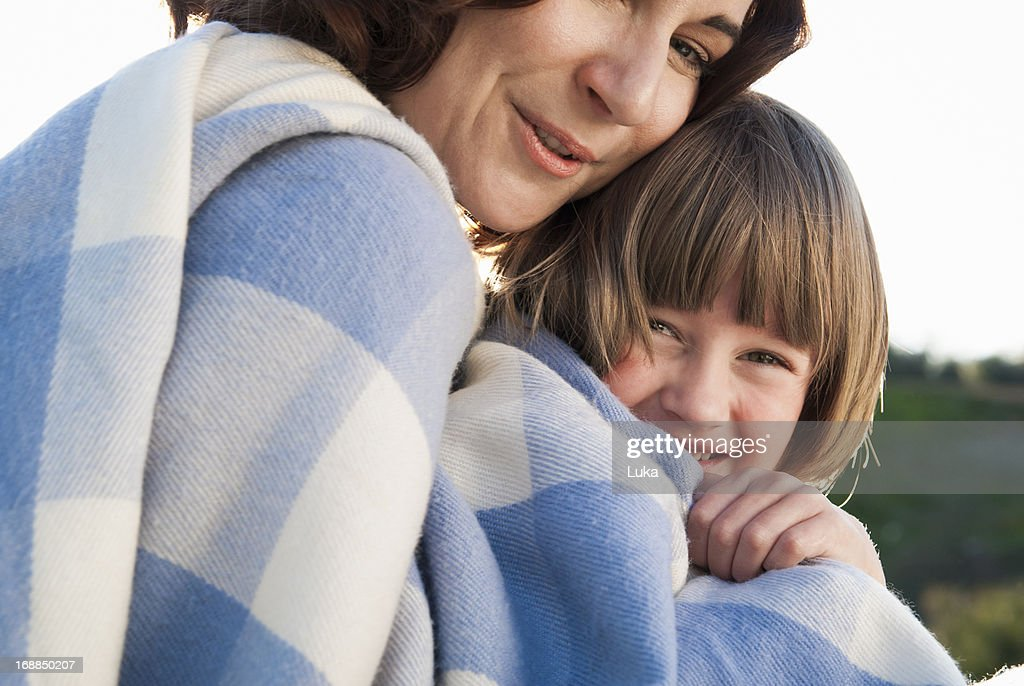 Mother and daughter wrapped in blanket : Stock Photo