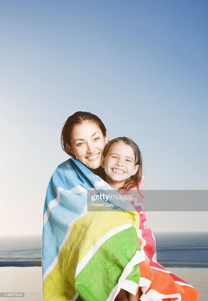 Mother and daughter wrapped in towel poolside : Stock Photo