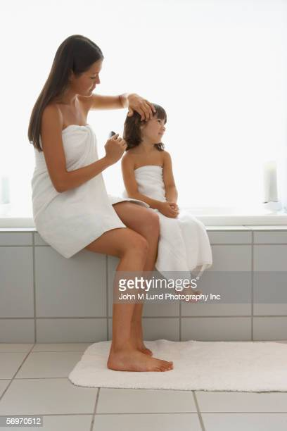 Mother and daughter wrapped in towels brushing hair