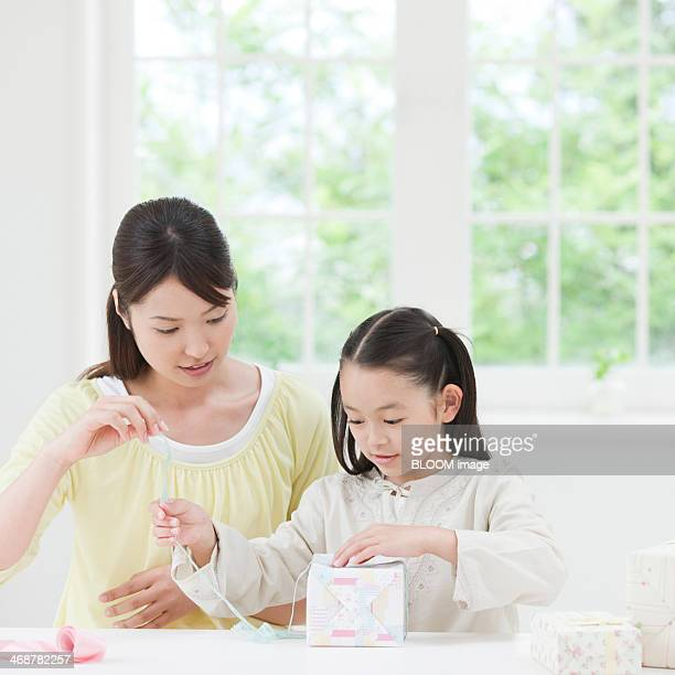 Mother And Daughter Wrapping Gift