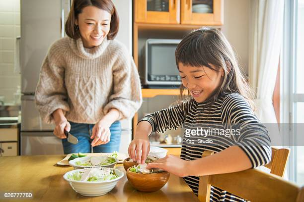 Mother and daughterl preparing for lunch in home.
