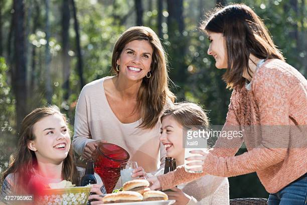 Mother and daughters at a picnic pouring lemonade