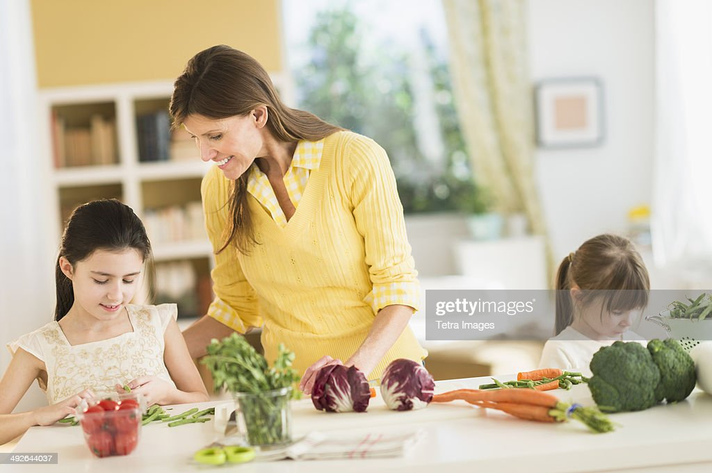 Mother and daughters (4-5,8-9) cooking in kitchen, Jersey City, New Jersey, USA : Stock Photo