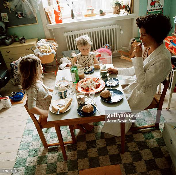 Mother and daughters eating dinner in a child room Sweden.