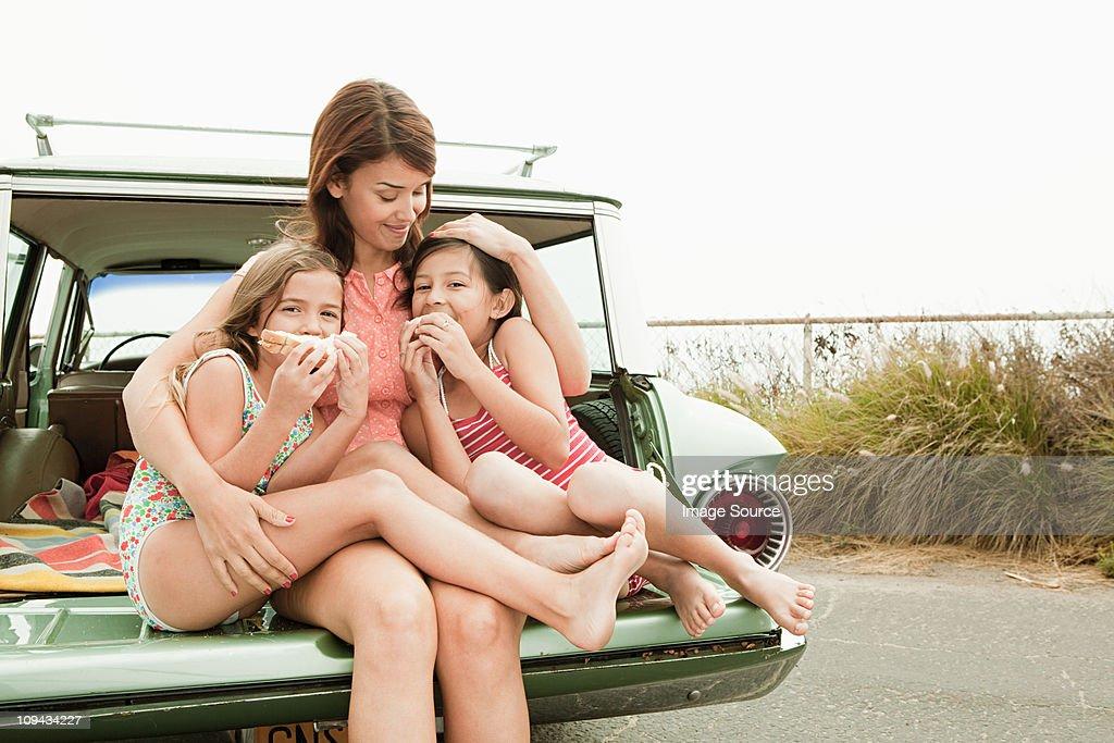 Mère et fille mangeant des sandwichs sur car boot : Photo