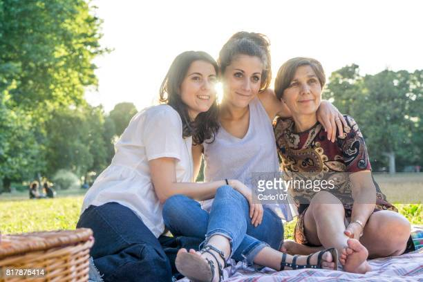 Mother and daughters embracing in a park during a picnic