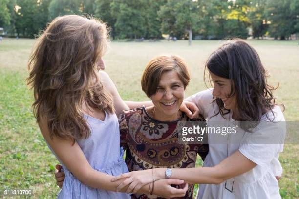 Mother and daughters embracing in a park