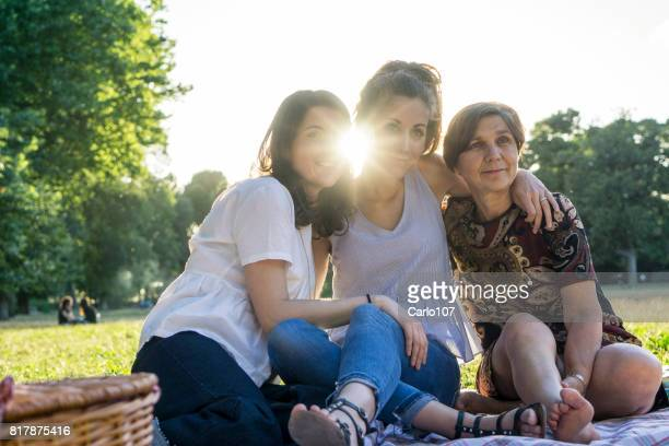 Mother and daughters embracing together in a park during a picnic