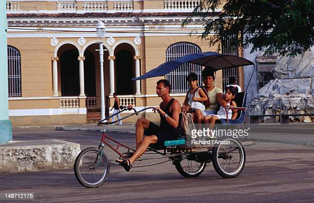 Mother and daughters grab a ride in a pedicab in Remedios.