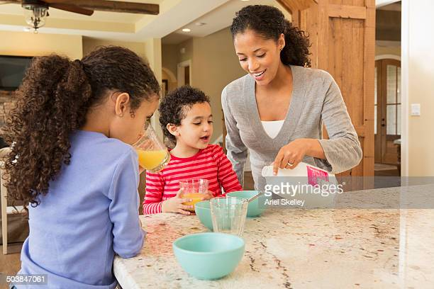 Mother and daughters having breakfast in kitchen