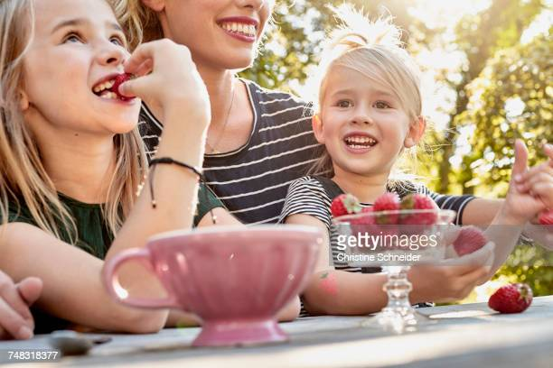 Mother and daughters having strawberries in garden