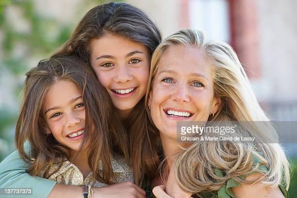 Mutter und Töchter, die sich umarmen im Freien
