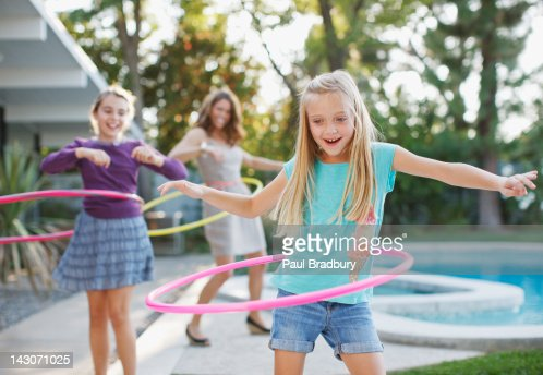 Mother and daughters hula hooping outdoors : Stock Photo