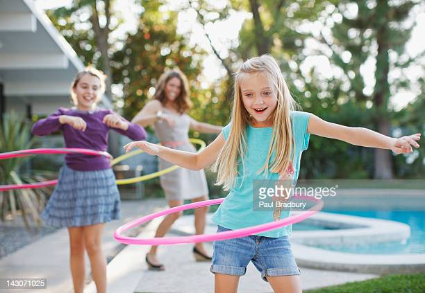 Mother and daughters hula hooping outdoors