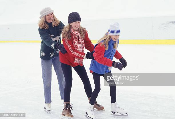 Mother and daughters (6-7) (12-13), ice skating