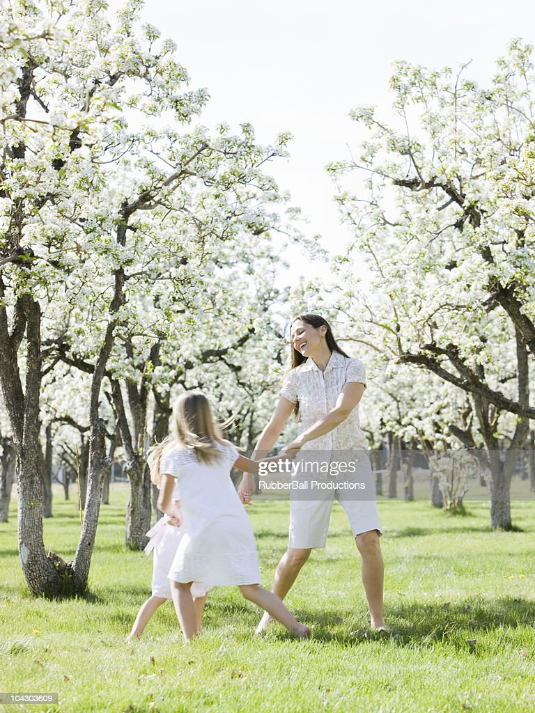 mother and daughters in a blossoming orchard : Stock Photo