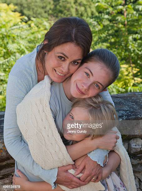 Mother and daughters in garden, hugging