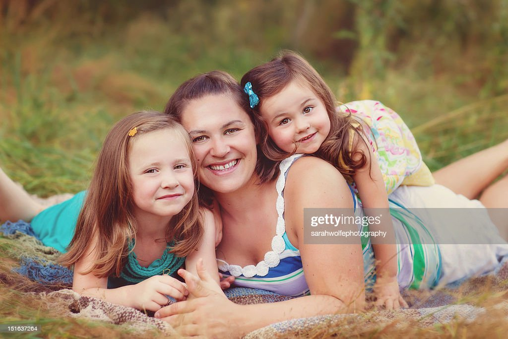 Mother and daughters in grass : Stock Photo