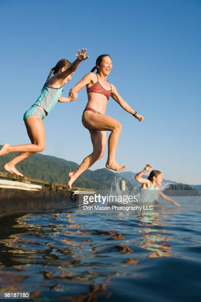 Mother and daughters jumping into lake