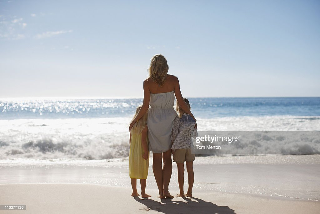 Mother and daughters on beach looking at ocean : Stock Photo