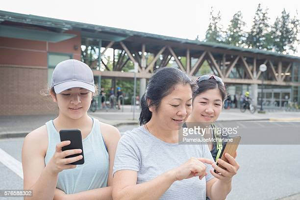 Mother and Daughters Playing Augmented Reality Game on Mobile Phones