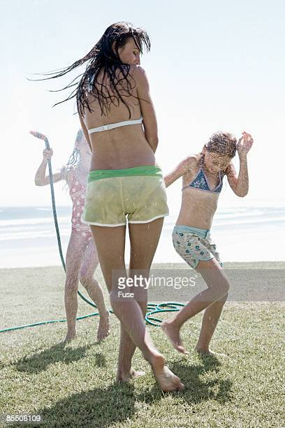 Mother and Daughters Playing in Garden Hose