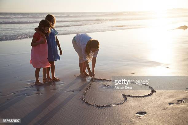 Mother and daughters playing on beach