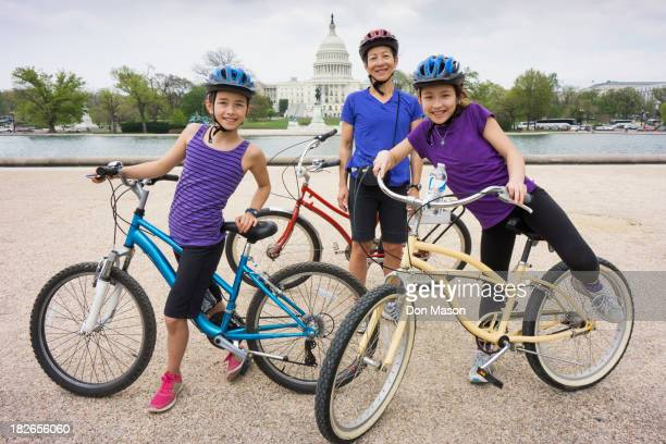 Mother and daughters riding bicycles by Capitol Building, District of Columbia, United States