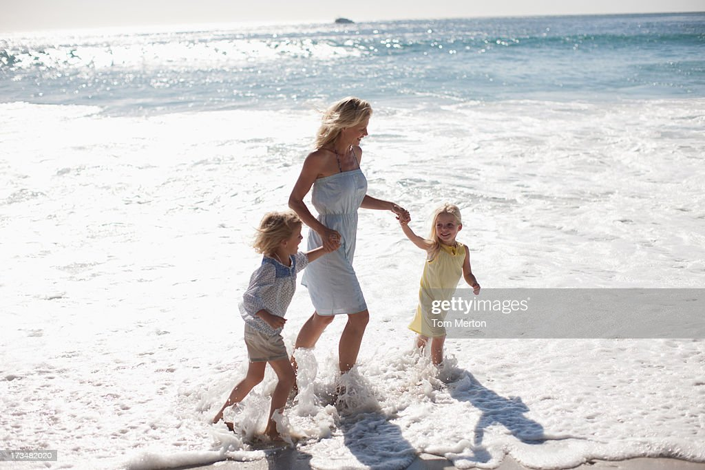 Mother and daughters running on beach : Stock Photo