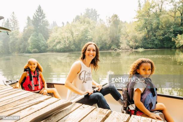 Mother and daughters sitting in canoe in lake