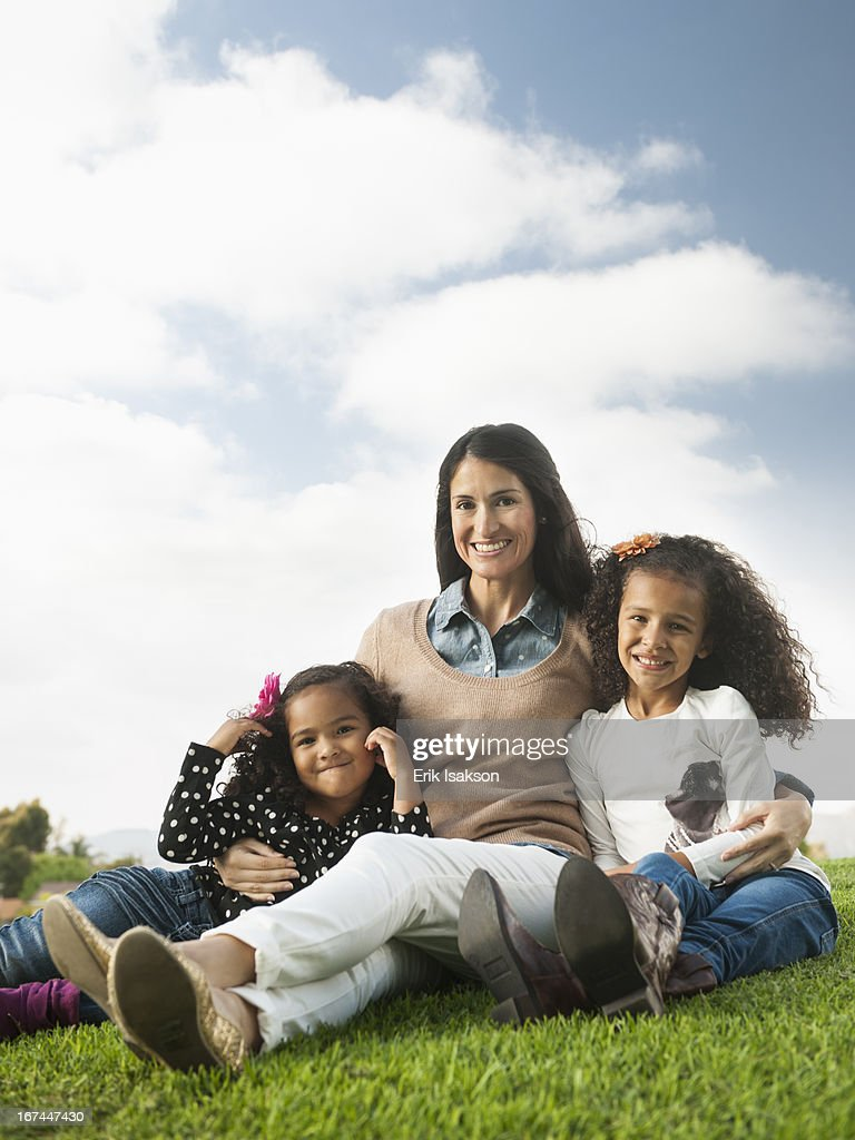 Mother and daughters sitting in grass : Stock Photo