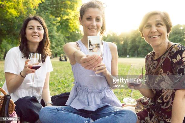 Mother and daughters taking a instant photo while drinking wine in a park during a picnic