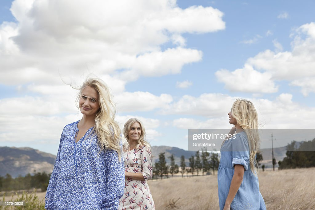 Mother and daughters walking in field : Stock Photo