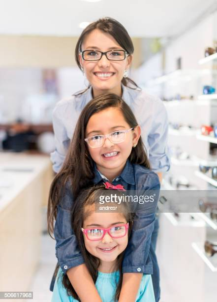 Mother and daughters wearing glasses at the optician